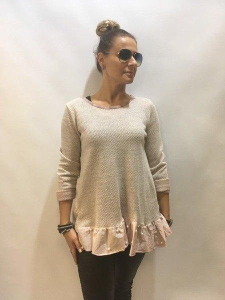 Sweter różowy z falbaną i perłami.